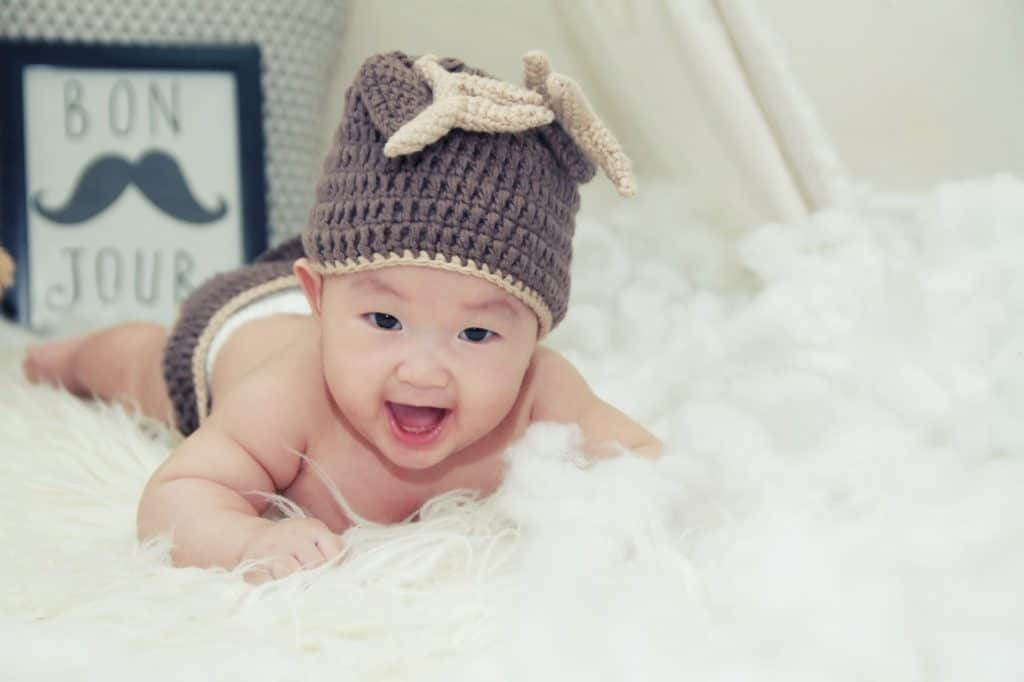 Chinese baby with a heat is crawling on a white rug