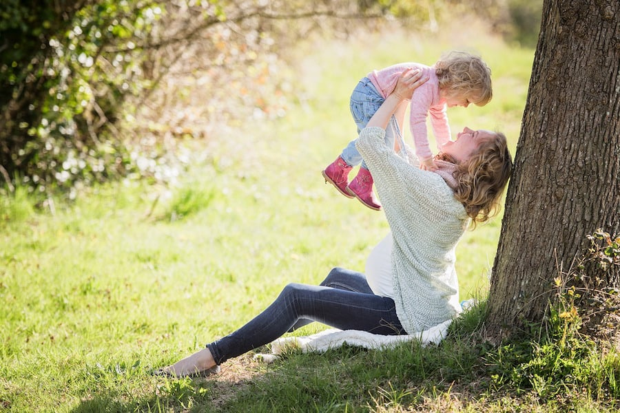 mother holding kid in park