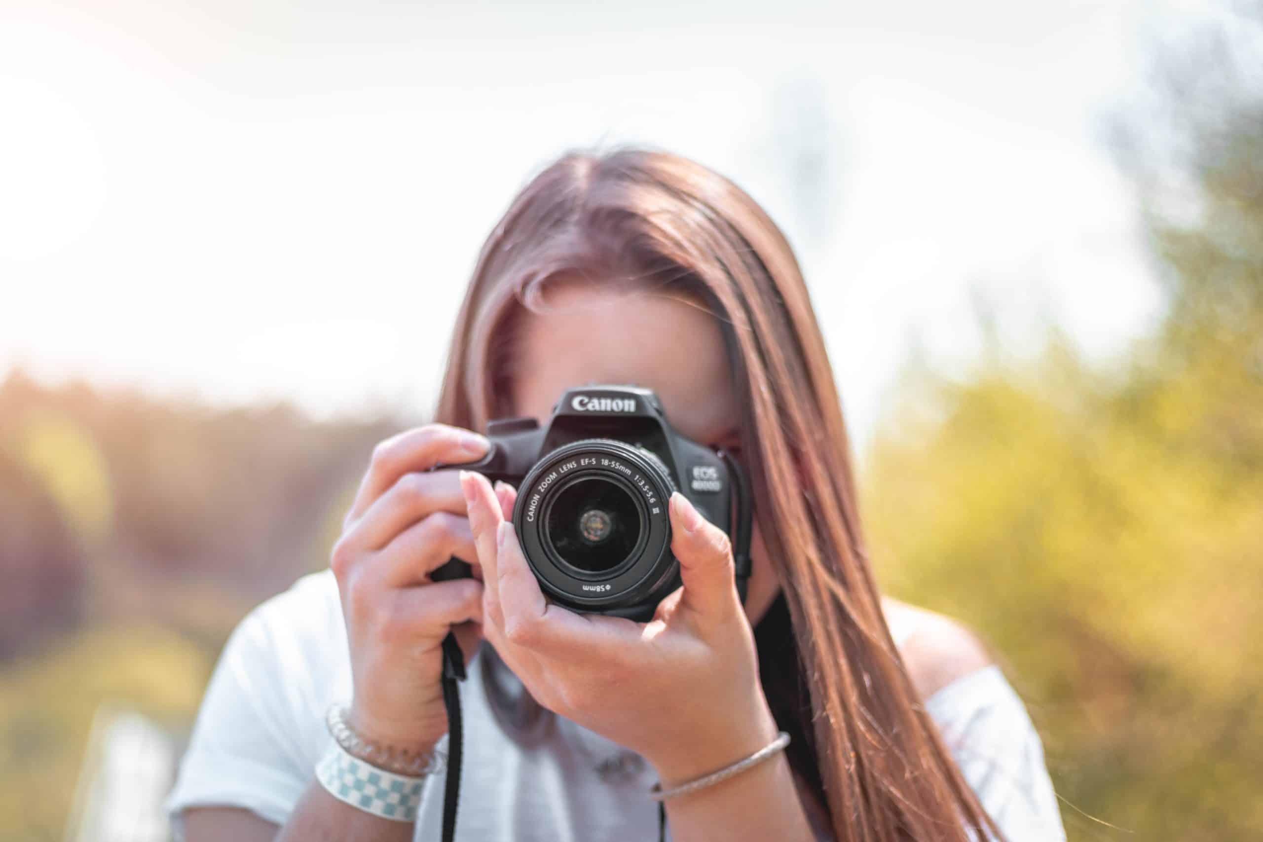 A woman taking a photo with a DSLR camera